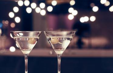 Pair of martini glasses on restaurant bar.