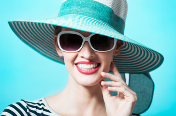 Fashion portrait of woman in hat smiling.