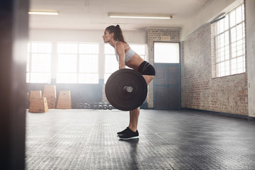 Fitness woman doing weight lifting at health club.