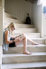 Sweden, Skane, Vejbystrand, Girl (10-11) reading book on wooden steps at home