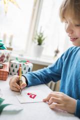 Boy (10-11) writing Christmas cards