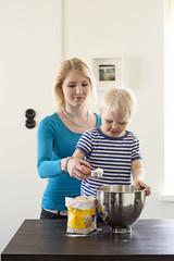 Finland, Helsinki, Kallio, Mother helping son add flour to mixer bowl
