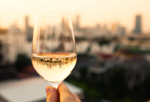 person enjoying a glass of wine and city view.