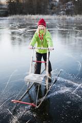 Sweden, Sodermanland, Nacka, Girl (8-9) with sleigh on frozen lake