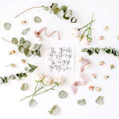 inspirational quote the greater your storm the brighter your rainbow written in calligraphy style on paper with pink roses and eucalyptus branches on white background. flat lay, top view