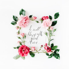 """inspirational quote """"what is done in love is done well"""" written in calligraphy style on paper with pink, red roses, chamomiles and leaves isolated on white background. Flat lay, top view"""