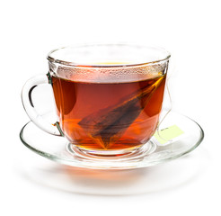 Transparent cup of tea with tea bag on white