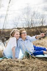 Finland, Keski-Suomi, Aanekoski, Girl (12-13) and boy (12-13) sitting on blanket outside and looking away