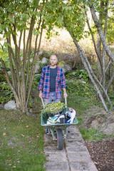 Sweden, Sodermanland, Nacka, Man pushing wheelbarrow in garden
