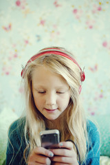 Sweden, Girl (6-7) listening to music on headphones, using cell phone