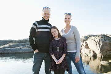 Sweden, Bohuslan, Smogen, Portrait of girl (8-9) standing with parents on rocky beach