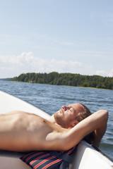 Sweden, Uppland, Stockholm Archipelago, Man sunbathing on boat