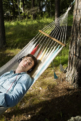 Sweden, Dalarna, Falun, Teenage boy (16-17) lying on hammock in forest