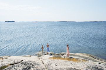 Sweden, Sodermanland, Stockholm Archipelago, Varmdo, Mother with sons (12-13) on rocky beach at sunny day