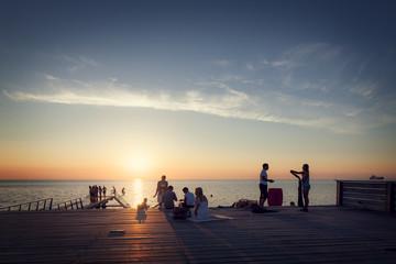 People enjoying on promenade during sunset