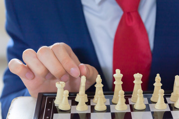 Business man moving chess figure with strategy and team leadership