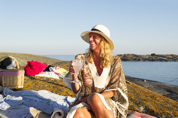 Sweden, Sodermanland, Stockholm Archipelago, Varmdo, Smiling woman with wine glass at rocky beach