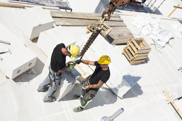 Sweden, Ostergotland, Linkoping, Construction workers adjusting blocks on construction site