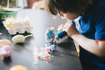 A child decorating eggs at Easter with glitter, glue and paint.