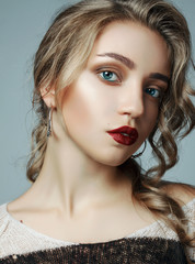 a large portrait of a very beautiful girl. girl with a professional make-up and a professional hair styling. girl with red lips, big eyes on a gray background.