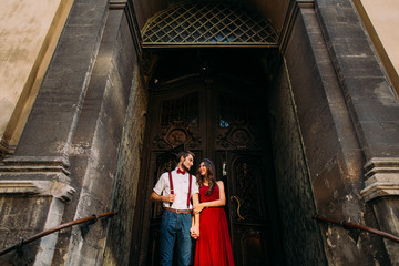Stylish luxury dressed couple posing in front of vintage old wooden entrance door at Lviv cathedral