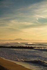 portrait view of atlantic ocean with mountain la rhune in the back in sunset, capbreton, france