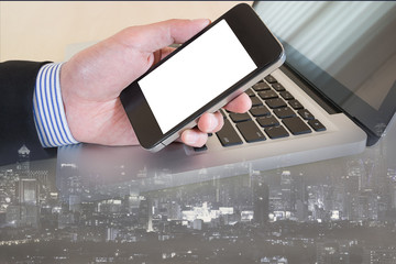 businessman hand on smat phone with cityscape background