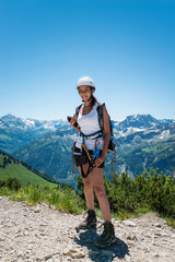 Smiling young adult in hiking outfit near mountain