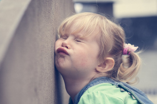 Baby girl banging the face against a wall