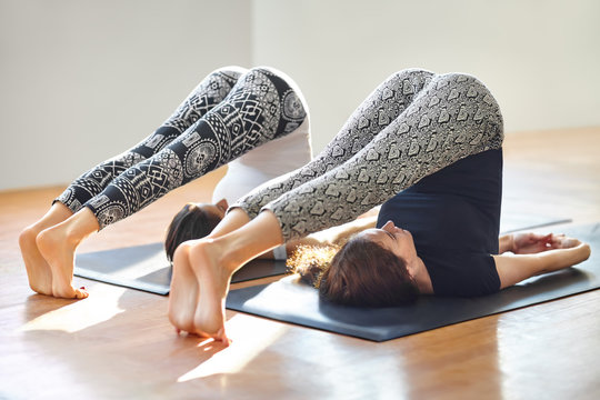 Two young women doing yoga asana plow pose