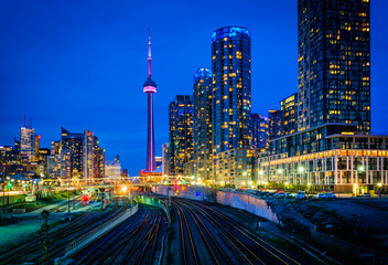 Wall Murals Toronto View of a rail yard and modern buildings in downtown at night, f