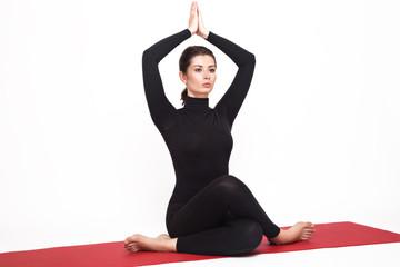 Beautiful athletic girl in black suit doing yoga. gomukhasana asana - pose cow's head. Isolated on white background.