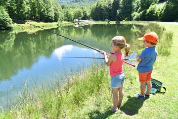 Kids fishing by mountain lake in summer