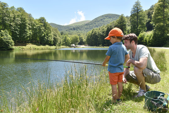 Father and son fishing together by mountain lake