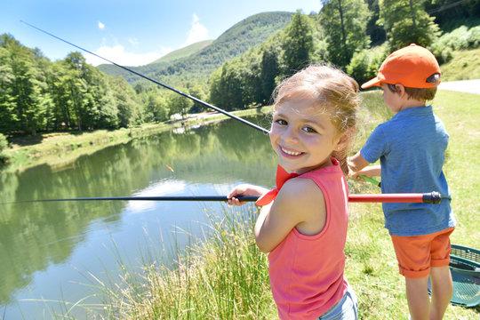 Portrait of little girl fishing by mountain lake