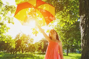 Happy redhead girl with umbrella in summer sun. Freedom, summer,