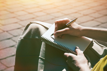 female girls hands with pen writing on notebook in park