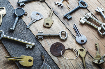 Old metal keys on a grungy wooden background.