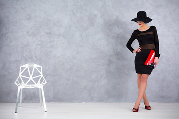 Shot of an elegant woman standing in a room next to a modern gap chair