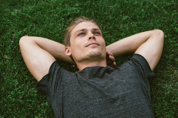 Obraz Attractive Young Man Lying with Both Hands Resting Behind his Ne - fototapety do salonu