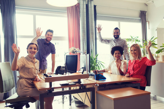 happy creative team waving hands in office