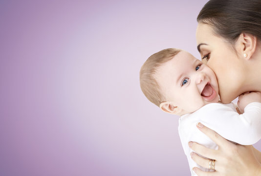 happy mother kissing adorable baby