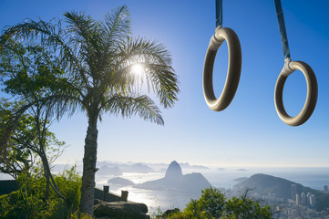 Gymnast rings hanging in bright sunset light above Sugarloaf Mountain and the city skyline in Rio de Janeiro, Brazil