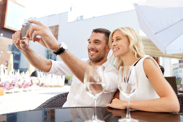 couple taking selfie with smatphone at restaurant
