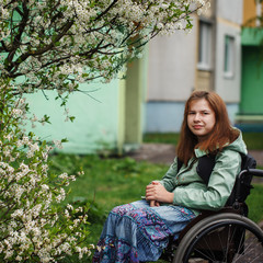 Portrait young woman in a wheelchair outside in spring day.