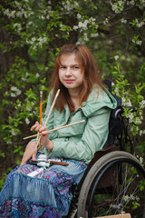 Young woman sitting in a wheelchair , smiling and holding brushe