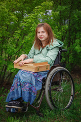 Young  woman in a wheelchair. The girl holds in hand an easel fo