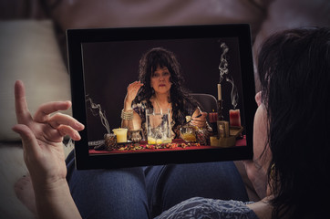 Woman reclines on sofa and talks with psychic online
