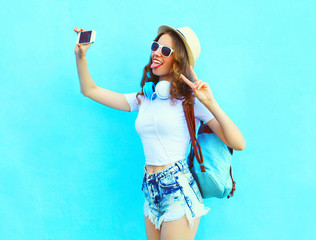 Fashion pretty cool girl makes self portrait on smartphone over