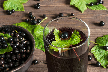 glass of cold black currant juice on wooden table with ripe berr